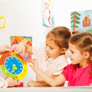 Two schoolgirls studying time, minutes and hours with the cardboard clock at the classroom